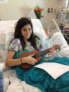 Child in hospital bed with ukulele