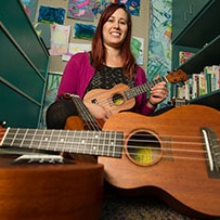 Tori Steely, UC Davis Children's Hospital music therapist, holding a ukulele donated by Ukulele Kids Club Inc.