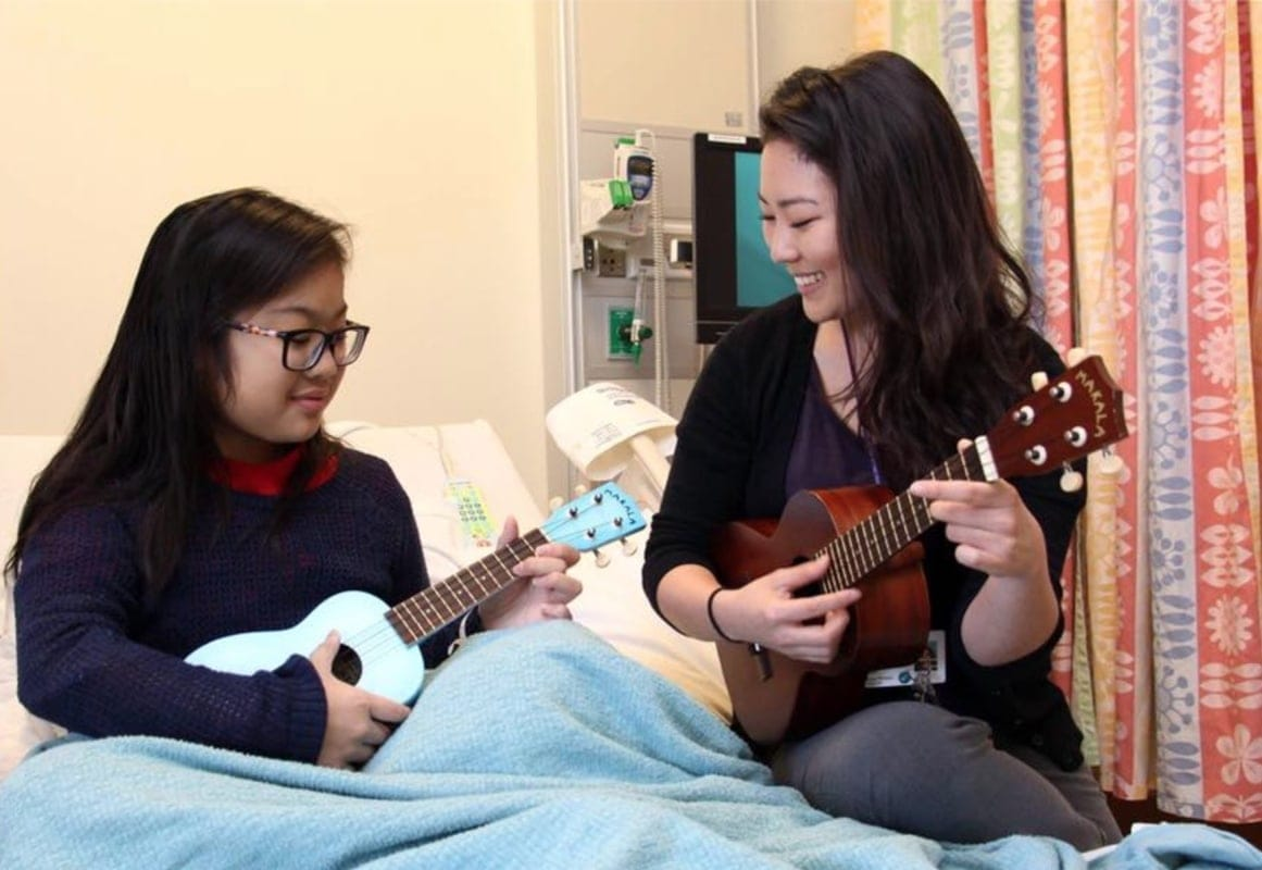 Music therapist sitting in hospital bed with young female patient, both playing ukuleles.