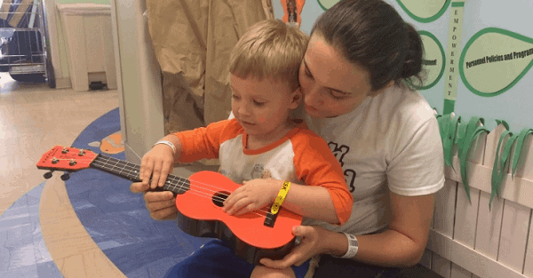 Music therapist showing a young male child how to play a ukulele