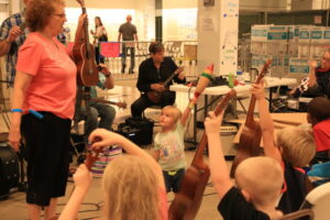 Children with ukes in their hand sitting on the floor learning to play with an adult woman instructor
