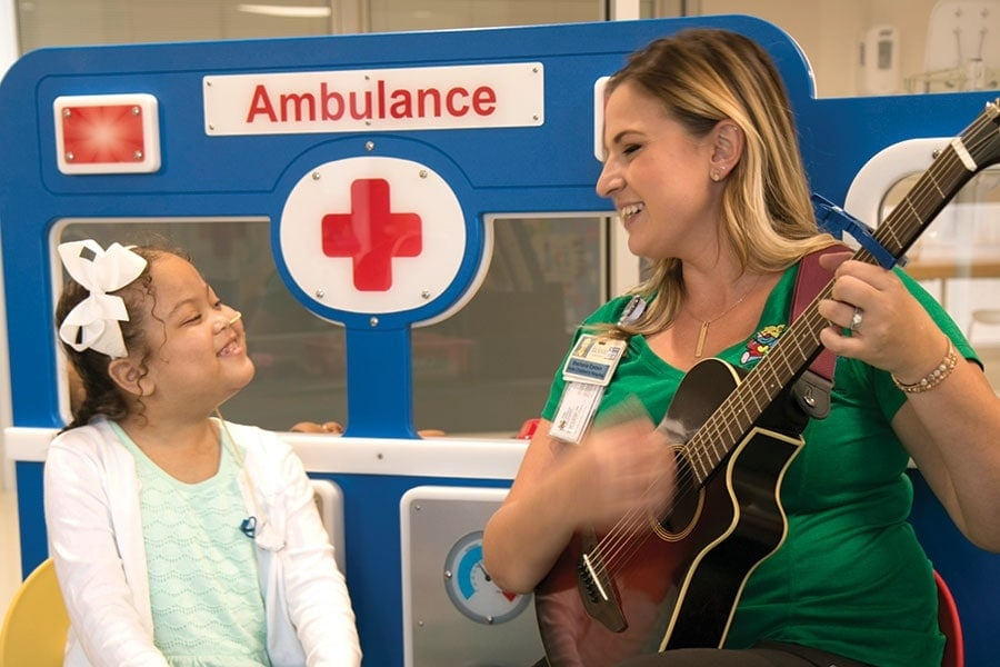 Stephanie Epstein singing to a smiling patient dressed in white