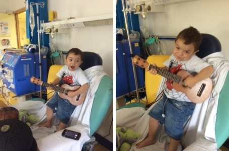 Child in hospital bed playing the ukulele